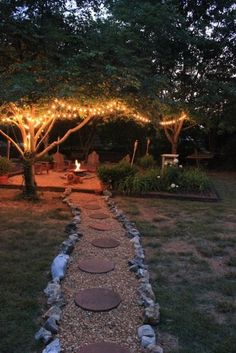 Beautiful decorating idea for a backyard firepit. Love the walkway and the lights in the trees. Perfect for a backyard barbeque or a wedding.