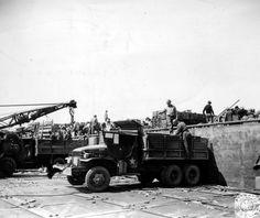 """Déchargement de matériel d'un ponton Rhino dans des camions GMC stationnés sur un causeway. Des civils et des militaires manutentionnent des caisses en bois (munitions ?) au moins deux militaires-un officier et un GI-sont du 5th ou 6th ESB (voir l'arc de cercle blanc sur le casque) secteur Omaha. Au premier plan un GMC 353 H1 Dump """"Genie"""" à treuil."""