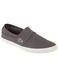 Lacoste Men's Marice Par in Dark Grey/Dark Grey Everyone loves a pair of great slip-on shoes. Unlike other traditional canvas shoes, these are left unlined for ultimate breathability and comfort, but also allow the collar to be incredibly light and flexible. Theres some elastic on the side for fit and comfort, but it has been craftily hidden. This shoe is minimalist style at its finest!