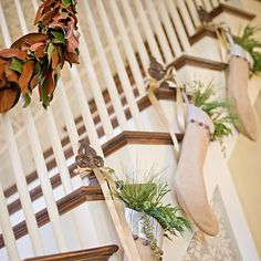 Stockings filled with evergreens as a garland on a staircase