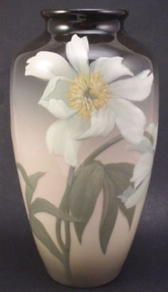 "Rookwood artist signed ""Sara Sax"" (monogram) dated 1908 fine American art pottery vase with large floral decoration in iris glaze. Marks include ""W"" incised for the white (iris) glaze with the Rookwood logo along with the shape number ""614D"" and the artist's monogram. Design features two large open blossoms and one closed blossom. Excellent condition with minor light scratches at shoulder. 11"" h x 3"" diam (at top). 5 1/2"" at widest."