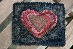 """This primitive hooked old heart rug/mat was hooked on linen using all hand dyed wools. The heart was hooked with a blend of primitive reds and for the background I used a nice mix of worn black hand dyed wools .This piece of folk art measures in at 6"""" x 5"""". 