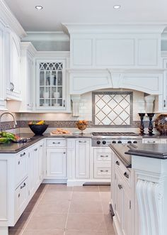 love the tile mosaic on all walls above the counter. Love the dark counter with white cabinets and like the hood above stove