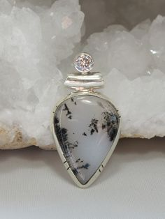 "Rare translucent polished Dendritic Opal pear-shaped gemstone pendant accented with a single faceted White Topaz gemstone, set in 925-sterling silver. Length: 1.5"" including bail. Width: .75"""