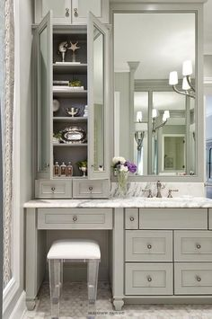 bathroom features gray vanity cabinets paired with a statuary marble countertop a lucite stool is tucked under a vanity topped with mirrored