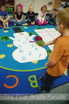 In this game, the kids had to toss a purple snowflake onto the snowman.  The tosser would read the number  on the snowman and then fill in that many frames on the tens frame with the snowflakes. The next person has to determine how many more to make 10.