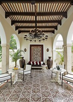 Spanish style outdoor space – love the ceiling design with planks, beams and corbels – floor tile –wrought iron chandelier
