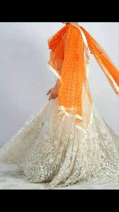The cream color lace lehenha and the brihht orange dupatta looks like a divine combination