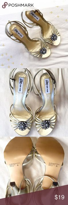 Gold Strappy Heels These are beautiful shoes by SM New York. The shoes are a shiny gold with fun rhinestone embellishment. I love these shoes but they are too small for me. 4 inch heel height with strap around the ankle. One rhinestone cluster is less shiny than the other but isn't noticeable unless you're looking up close. Only tried on, a few scuffs from storage. SM New York Shoes Heels