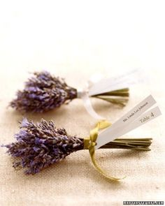 Lavender Seating Cards: For an aromatic seating card, two strips of paper -- with the guest's name printed on one end and the table number on the other -- are tied with satin ribbon to lavender wrapped with floral tape.