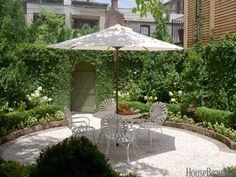 The walled courtyard garden is lush with jasmine, hydrangeas, orange trees, and creeping fig.crushed oyster shells cover the ground. The iron table and antique French garden chairs are shaded by a Pottery Barn umbrella. Garden design by Marshall Stone. Backyard Garden Landscape, Backyard Landscaping, Landscaping Ideas, Pergola Ideas, Backyard Gazebo, Garden Spaces, Outdoor Rooms, Outdoor Living, Outdoor Decor