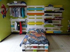 Esta habitación se encuentra con muebles realizados en su totalidad con palets. La cama, el cabecero y el sector de armario, todo creativo de manera práctica y colorida donde se han combinado tonalidades como el celeste, amarillo, naranja y rojo para aportar detalles al color blanco que se ha utilizado como base del mobiliario.