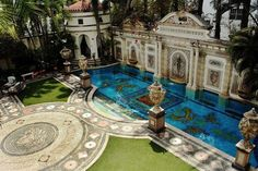 The pool at the Versace mansion, Casa Casuarina, in Miami Beach lined in 24-karat gold, numerous frescos, ornate statues, arched doorways and an open air courtyard.
