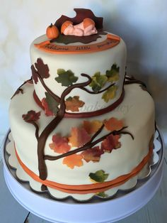 Fall Themed Baby Shower - The bottom tier was vanilla cake with a cherry filling and vanilla buttercream frosting while the top tier was banana cake, filled and frosted with brown sugar buttercream. The cake topper - the sleeping baby with a pumpkin hat lying on a curling maple leaf in variegated shades of green and maroon that look like the leaf is just turning colors, and the squat little pumpkin next to the baby, were all custom made. :D The entire cake is edible as usual.