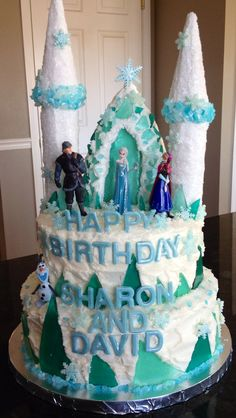 Disney Frozen Cake by Cakes By Clarke. Pretty shades of blue, white and green rock candy used to simulate ice. Castle cake. Disney princess cake. Queen Elsa, Princess Anna, Kristoff and Olaf on the cake. Delicate snowflakes cover the cake.
