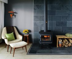 Black woodstove with large dark gray slate hearth, contrasting light tile flooring. Gray walls. Firewood box on side with pillow on top. Sophisticated design with just a touch of the rustic in the wood box. I love the orange lamp that echoes the fire and the orange in the kindling holder. Very pleasing.