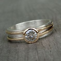 A beautiful carat) moissanite sits in a gold bezel on a wide…
