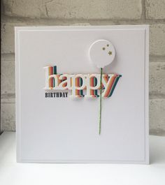 "I love the simplicity of this card!  A white panel on top of a white card base looks so clean with the ""happy"" rainbow on top of it.  Die cut the word in different colors and then stack them, showing only a smidge of each color.  Pop up a single balloon and you're done with your handmade birthday card."