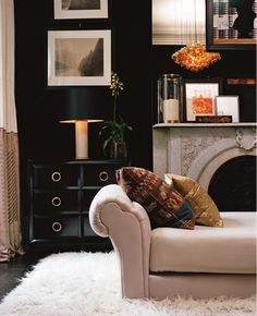 gray & black dramatic living room design with black wall paint color! Glossy black lacquer chest cabinet with round gold pulls, black leather lamp shade with alabaster base, twp tone silk drapes panels curtains, vertical photo gallery, velvet settee, white flokati rug, espresso wood floors, stone fireplace and wall mirror. Black walls paint color! Black white beige orange gold living room colors.