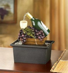 An endless sparkling cascade flows from the neck of a vintage wine bottle; clustered faux grapes add luscious color to this tasteful tabletop fountain. Wine Theme Kitchen, Grape Kitchen Decor, Kitchen Themes, Kitchen Utensils, Country Kitchen, Tabletop Fountain, Indoor Fountain, Affordable Home Decor, Cheap Home Decor
