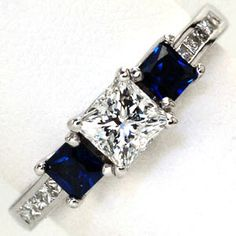 Tricia - Tricia is a eye-catching princess cut three stone design. Two colorful blue sapphires are positioned on either side of a 0.50 carat...