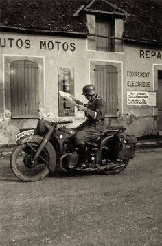 A German Army motorcyclist pauses to read a map somewhere in France. Note the…