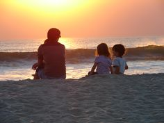Mother watching the sunset with her kids in Carlsbad State Beach.