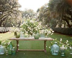 Decoración con botellones de cristal y flor de temporada.