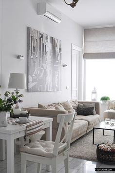 A soothing all-neutral living room with plush sofa, white desk and chair and black metal coffee table