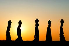 indian women carrying water pots at sunset