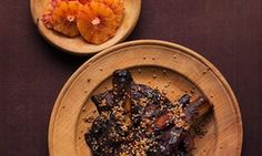 Dark brown tamarind pork ribs with a covering of seeds on a plate and a dish of orange slices next to it.