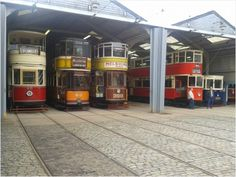 A selection of trams in the tram depot at Crich Tramway Village in Derbyshire.