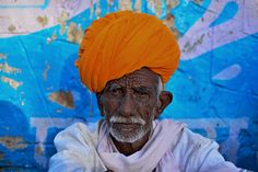 In the village - Portrait for Indian man in Pushkar, Pushkar is a town bordering the Thar Desert, in the northeastern Indian state of Rajasthan. It's set on Pushkar Lake, a sacred Hindu site with 52 ghats (stone staircases) where pilgrims bathe. The town has hundreds of temples, including 14th-century Jagatpita Brahma Mandir, dedicated to the god of creation, which has a distinctive red spire and walls inlaid with pilgrims' silver coins.