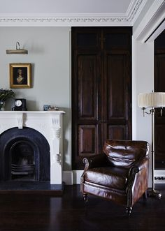 that leather chair, dark fireplace, dark wood floors, brass picture light, gold-framed portrait