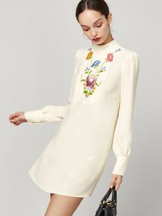 I'm not as sweet as I seem. This is a loose fitting, mini length dress with embroidery and a high neck.