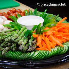 Fresh vegetable tray with mushrooms, asparagus, carrots, peppers, tomatoes, and cucumber.