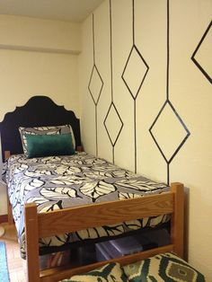 """Dorm room """"wallpaper"""" made with black tape and a wall decal sticker """"headboard."""""""