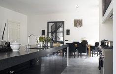 Moderne,zwarte keuken van Lodder met vrijstaand fornuis. Wanneer je in de keuken een nis hebt, kun je deze perfect gebruiken om een vrijstaand fornuis in te plaatsen. Deze keuken is verder uitgevoerd in prachtig zwarte hoogglans en een natuurstenen aanrechtblad. Allebei de spoelbakken zijn voorzien van een eigen kraan. Kortom alles om hier een superluxe keuken van te maken.