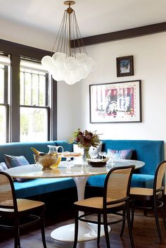 Modern dining space with blue sofa and bubble light fixture