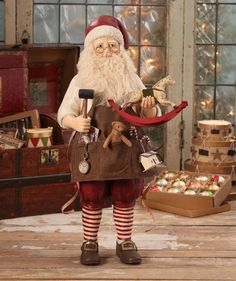 Get a glimpse of the toys and gifts Santa creates at his workshop. Old Fashioned Workshop Santa holds a toy rocking horse and mallet. A pocket watch and some of his creations; a storybook, teddy bear,