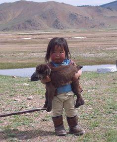 Adorable Mongolian girl and her baby lamb