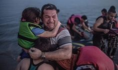 Syrian refugee Laith Majid holds his son and daughter, after arriving via a flimsy inflatable boat crammed with about 15 men, women and children on the shore of the island of Kos in Greece on 15 August 2015