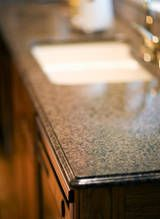 To keep granite countertops clean,  Once a week wipe down with a damp cloth and a stone cleaner formulated with a neutral pH. Never use harsh chemicals or abrasive cleaners. They can scratch, pit, and etch the surface of the stone. For oily stains, try a poultice made of a cup of flour or baking soda and 5 tablespoons of dish soap. Add water to make it the consistency of sour cream or yogurt. Place the solution directly on the stain and cover with plastic wrap overnight, before washing.