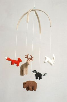15 Decor Ideas For Creating A Woodland Nursery Design // A mobile made from tiny knit animals will keep your baby entertained and tie in with the rest of the woodland pieces you've included in the nursery.