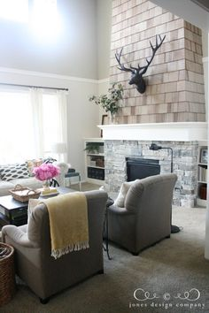 Jones Design Company living room with the finished stone & shingled fireplace + bookcases flanking it. Two tone walls separated by crown molding for 2 story rooms.