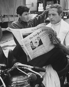 Paul Newman sits on a motorcycle reading a newspaper while he receives a spontaneous trim from Barber Jay Sebring on the set of Harper, 1965. Find out how to keep on top of your grooming this winter, on TheRake.com now.