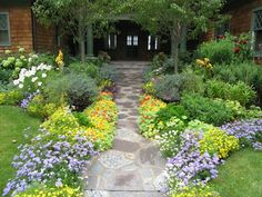 yard with brown stones path surrounded with yellow flowers and green plants on both side, grass on both sides of Landscaping Ideas for Small Spaces to Large Spaces