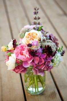 Variety of Blooms Switch off between placing bold peonies and smaller flower varieties in a clear vase for an arrangement that is loaded with texture.
