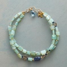 """JOURNEY TO PERU BRACELET @ Sundance.com Item No. 72604$228.00 You'll love the iridescent shimmer of this stunning Peruvian opal gemstone bracelet. Peruvian opals, squared and irregular, host smoky quartz, kyanite and London blue topaz. Two strands join with a 14kt gold plate hook clasp. Bracelet handmade exclusively for Sundance. 7-1/4""""L."""