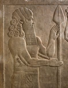 Spirit 'lahmu' (detail), his hair is arranged in elaborate ringlets, an ancient style, seen on semi-divine figures, the tassels hanging from his kilt also indicate divine status, he balances a spear on the ground, and the sheath of his dagger is carved with an animal's head, gypsum wall panel relief, North Palace, Kouyunjik, Nineveh, Iraq, neo-assyrian, 645BC-640BC